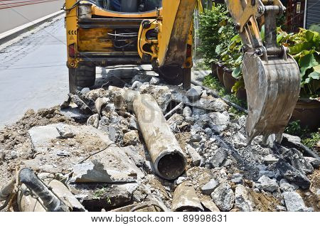 Backhoe Digging Asbestos Cement Pipe.