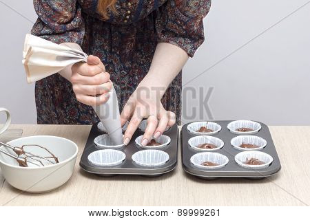 Cooking and home concept - close up of hand filling cupcakes molds with dough