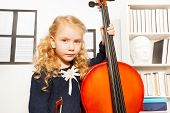Blond girl with curly hair holding the fiddle-bow to play violoncello in musical school poster