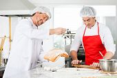 Smiling male chefs preparing ravioli pasta together at counter in commercial kitchen poster