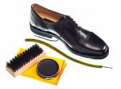 Shoe shine concept with shiny black shoe and polish, brush and cloth t-shirt
