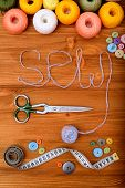 "Word ""sew"" with sewing tools and accesories on wooden background poster"