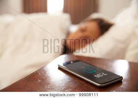 Woman Asleep In Bed Woken By Alarm On Mobile Phone