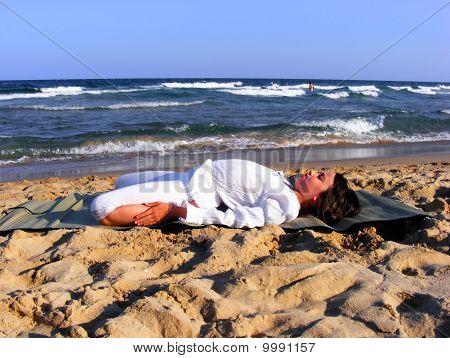 Young girl doing yoga on the beach