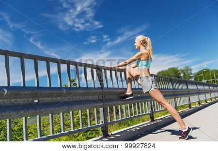 fitness, sport, exercising and healthy lifestyle concept - smiling woman stretching leg outdoors poster