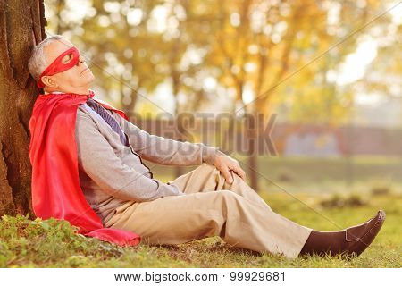 Senior in superhero outfit leaning on tree in park