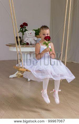 Portrait Of Little Cute Ballerina On Swing With Rose. Princess Concept. Fairy Tail