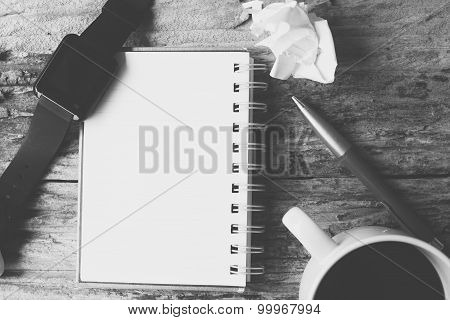 Blank notepad and smartwatch with hot coffee on office table poster