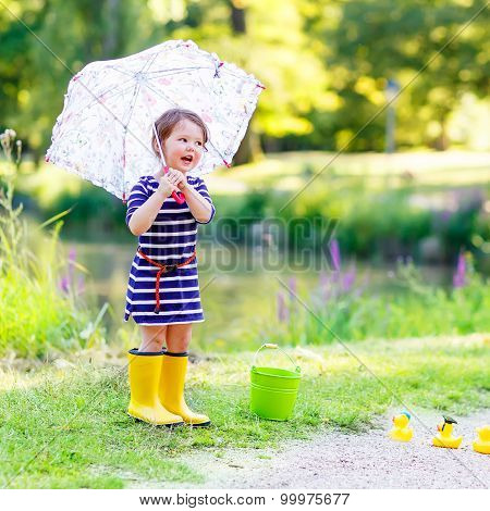 Cute Little Kid Girl In Yellow Rainboots In Summer Park