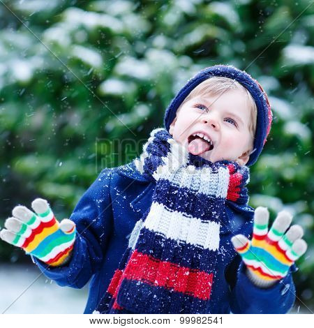 Cute Little Funny Boy In Colorful Winter Clothes Having Fun With Snow, Outdoors