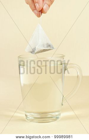 Hand with the tea bag above cup of hot water