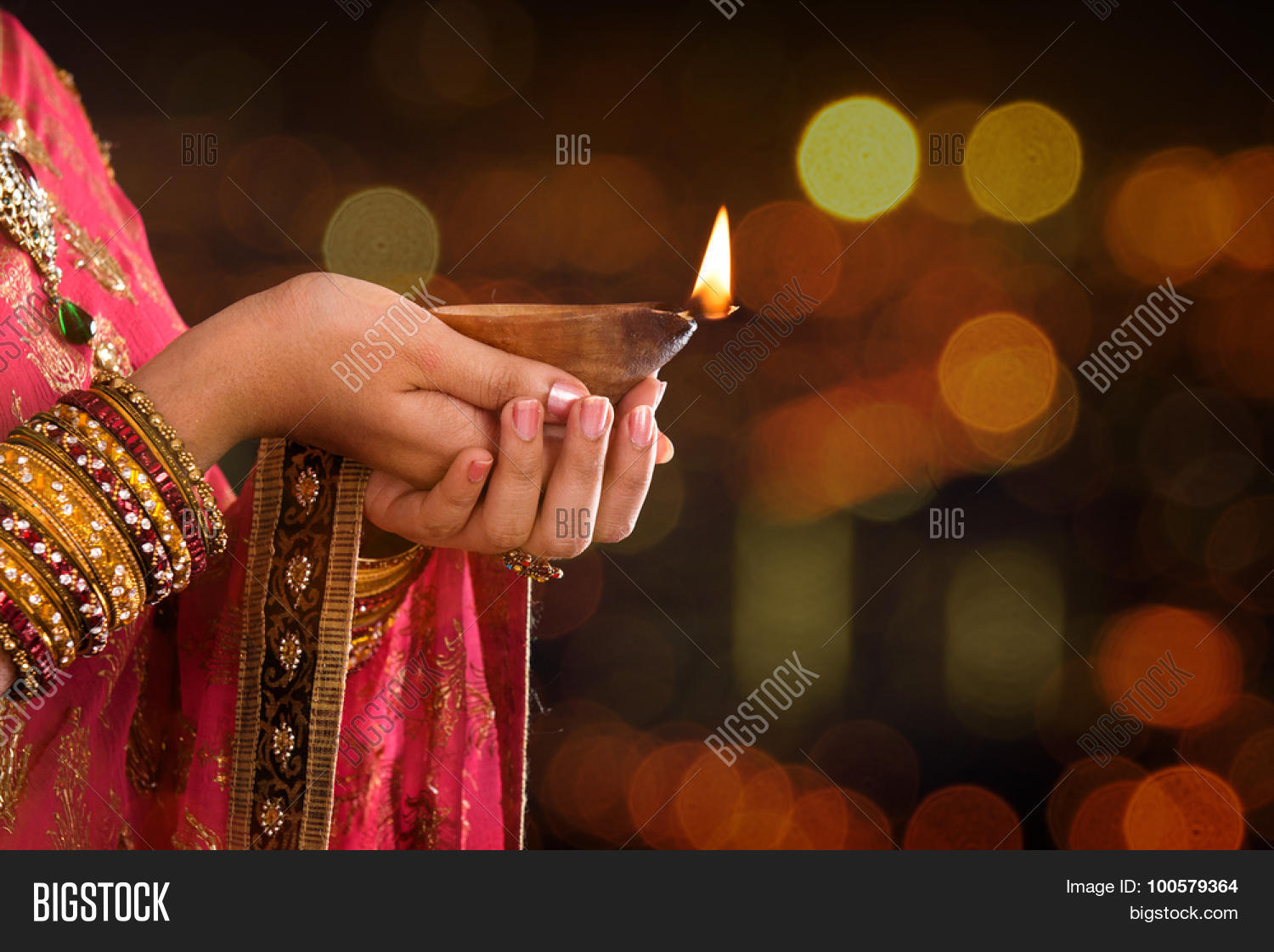 close up indian woman in traditional sari lighting oil lamp and