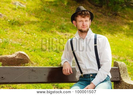 Young Man Retro Style Sitting On Bench In Park
