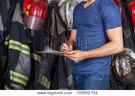 Midsection of fireman writing on clipboard at fire station
