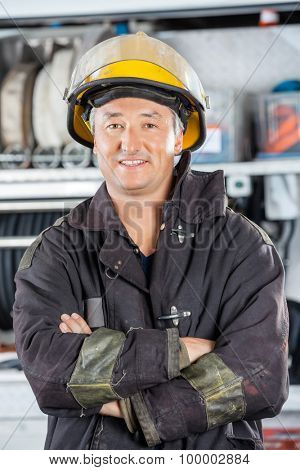 Portrait of happy mature fireman standing arms crossed at fire station