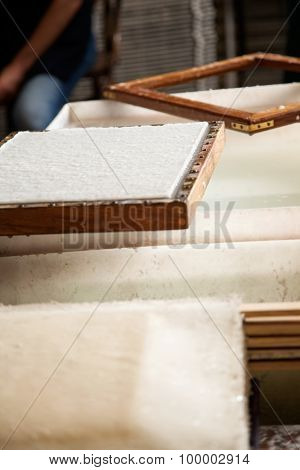 Closeup of paper on mold over pulp and water vat in factory