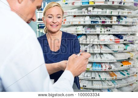 Smiling pharmacist explaining product details to customer in pharmacy