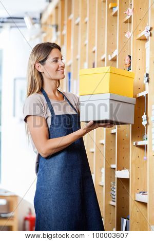 Smiling mid adult saleswoman keeping cardboard boxes in shelves at store