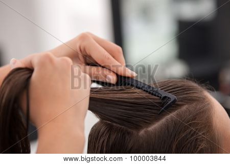 Professional young hairdresser is working with a comb