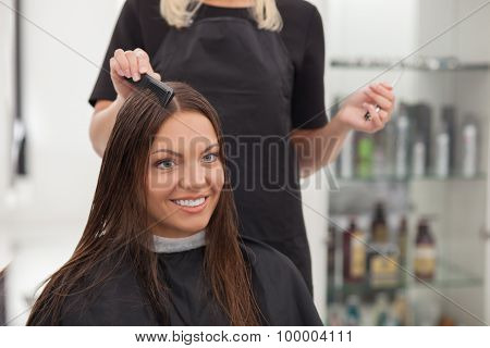 Attractive young woman is attending a beauty shop