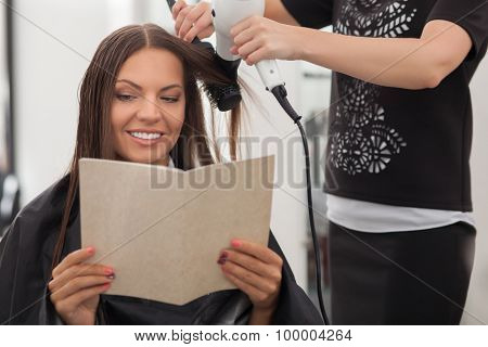 Cheerful young hairdresser is making a hairstyle for her customer