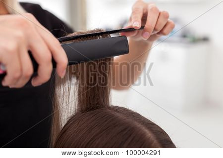 Cheerful young hairdresser in making female hair smooth