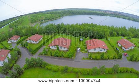 Several cottages on lake shore at summer cloudy day. Aerial view