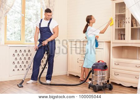 Cheerful young workers are cleaning the house with joy