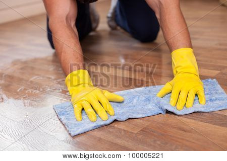 Skilled young cleaner is mopping floor in a house
