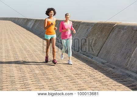 Two smiling sporty women jogging together at promenade