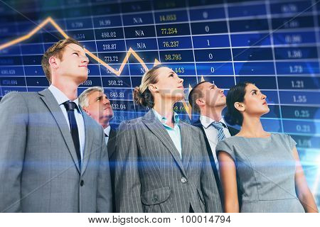 Business team looking up against stocks and shares