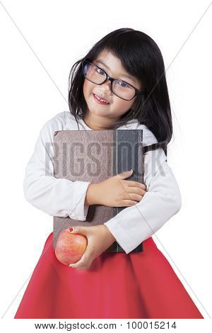 Adorable Little Girl Holds A Book And Apple In Studio