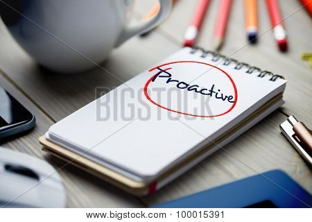 The word proactive against notepad on desk