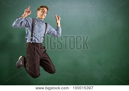 Geeky hipster jumping and pointing against green chalkboard