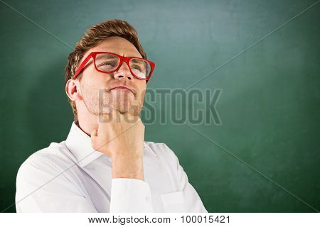 Young geeky businessman with hand on chin against green chalkboard