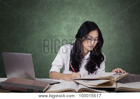 Attractive Learner Writing On The Book In Class