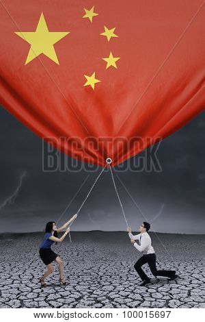 Businesspeople Pulling Down A Chinese Flag