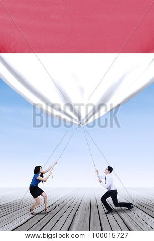 Businesspeople Pulling Down Indonesian Flag