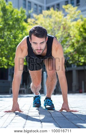 Portrait of an athlete in running stance on a sunny day