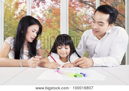 Creative Child Studying With Parents At Home