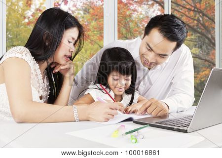 Cute Girl Learn To Write With Parents At Home