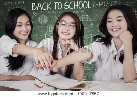 Group Of Female Students Stacking Hands In Class