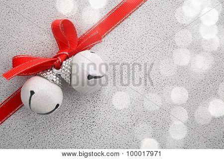 White jingle bell with ribbon bow on festive background