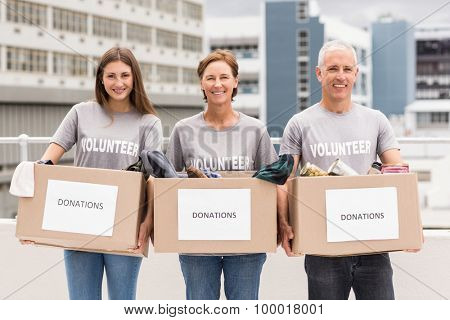 Portrait of smiling volunteers holding donation boxes on roof of building