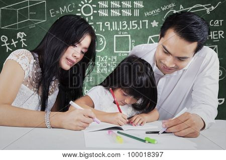 Kid Learning In Class With Two Teachers