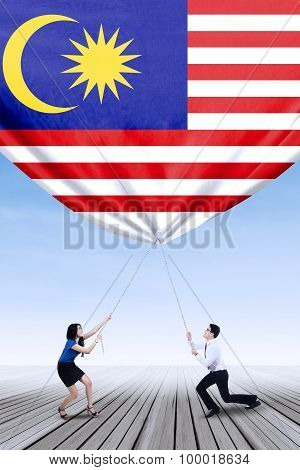 Man And His Partner Pulling Down Malaysian Flag