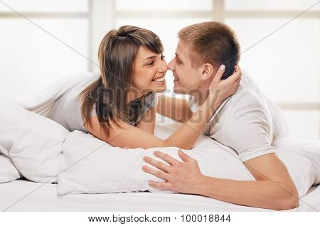 Couple lying in bed embrace