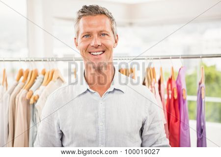 Portrait of smiling man in front of clothing rail in clothing store