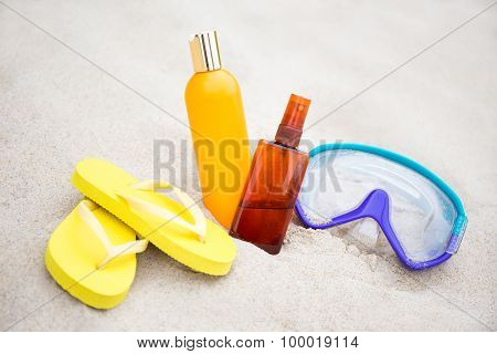 Summer Concept - Close Up Of Flip Flops, Suntan Lotion Bottles And Diving Mask On The Sand