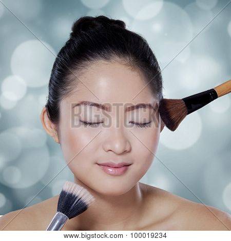 Pretty Girl Using Makeup Brushes In Studio